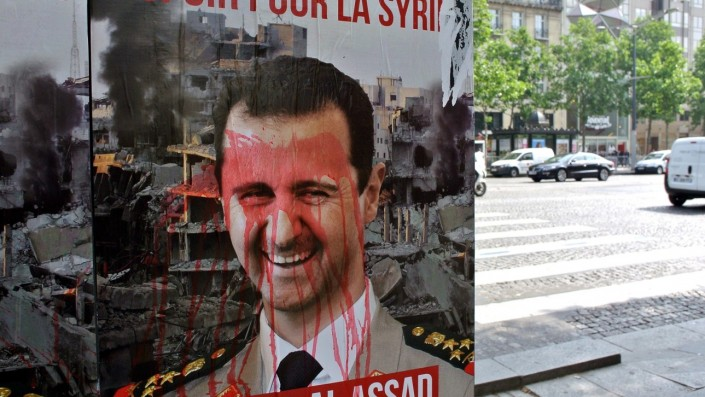 """A poster mocking Syrian president Bashar al-Assad is seen on the Champs Elysees avenue in Paris, on June 2, 2014, a day before the presidential election in Syria. Syria geared up today for an election expected to keep Assad as president but derided as a """"farce"""" and only staged in regime-held parts of the war-ravaged country. AFP PHOTO/AMMAR ABD RABBO == NO SALE == NO MAGAZINES ==        (Photo credit should read AMMAR ABD RABBO/AFP/Getty Images)"""